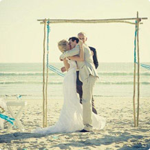 a new couple kiss each other for their wedding at the beach