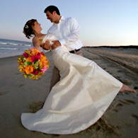 Groom hold his bride whose hand holds a bouquet without shoes